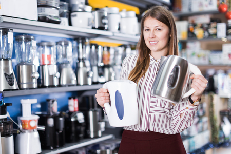 Smiling female seller showing two kettles in a domestic appliances section 免版税图像