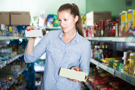 Portrait of adult woman in the shop holding preserved of tuna Stock Photo