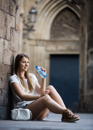 Smiling young woman sitting near old stone wall drinking water from bottle