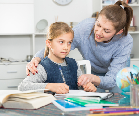 Attractive woman helping her daughter to do her homework at home Stockfoto