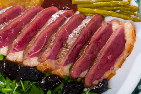Tasty grilled duck magret fillet served with greens, prunes, asparagus and sauce