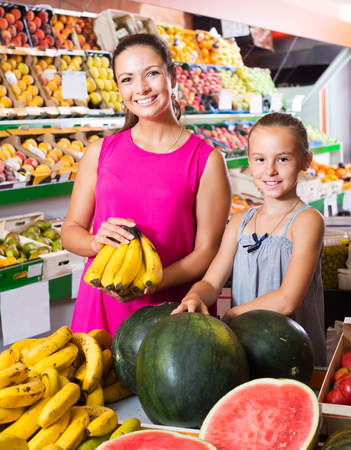 Smiling woman with little daughter buying bananas in fruit section in supermarket Zdjęcie Seryjne