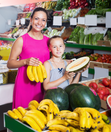 Happy family of woman and girl taking various fruits in food shop