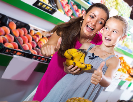 Woman with girl looking satisfied and holding thumbs up  in grocery shop Zdjęcie Seryjne