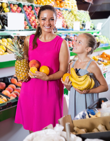 Cheerful young female with girl buying various fruits in marketplace Zdjęcie Seryjne