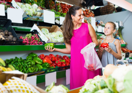 Smiling woman with daughter choosing green and red paprika in food shop