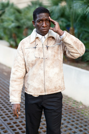 Portrait of confused mature African man in urban environment