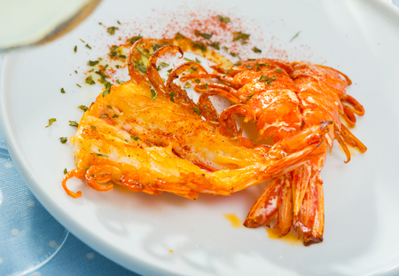 King fried prawns with parsley and spice on a white plate