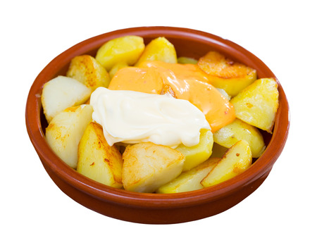 Spanish cuisine. Delicious deep fried potatoes (Patatas bravas) with two sauces in clayware. Isolated over white background
