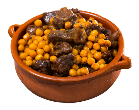 Beef stew with chickpeas in a clay plate. Isolated over white background 스톡 콘텐츠