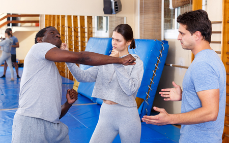 Young people practicing in pair self-defence movements with male trainer supervision