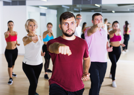 Smiling people of different ages studying sport dance elements in dancing class