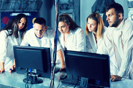 Five positive european adults solving conundrums together in quest room in view as abandoned lab
