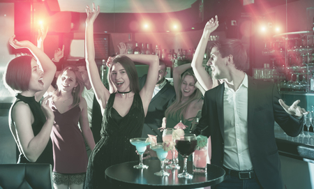Young students dancing on event with cocktails in the club