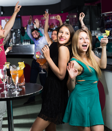 Portrait of cheerful females and males having fun in the bar