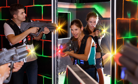 Nice Laser tag players young mens and womens playing in teams in dark laser tag station Banque d'images