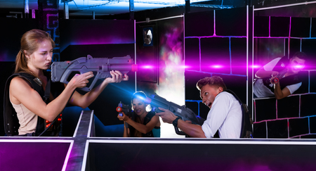 Laser tag players standing opposite each other with laser guns in dark room
