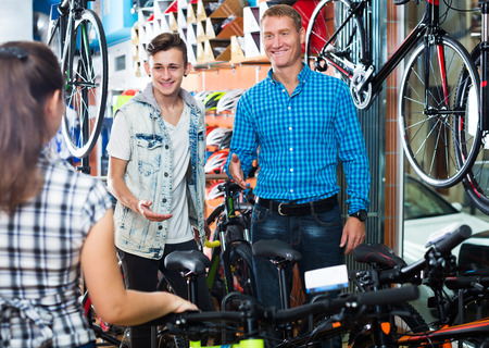 Father with young teenager boy asking female seller for help in sport bike shop Stock fotó