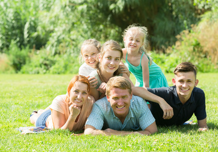 Portrait of big smiling family with parents and four children lying together on green lawn outdoors