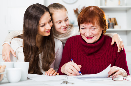 Portrait of friendly happy family sitting at home table, working with papers