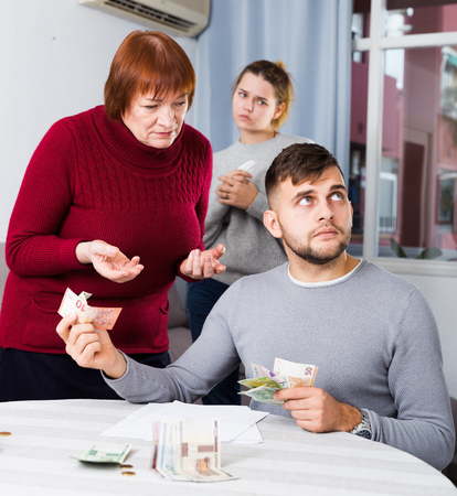 Elderly mother asking adult son for money while his upset sister standing behind