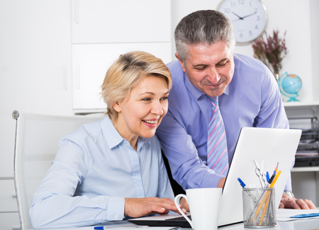 Mature man helping his colleague to prepare document on your computer