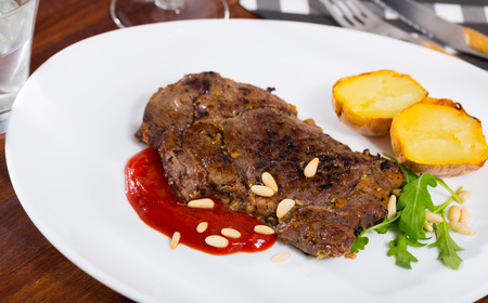 Beef steak with ketchup and pine nuts, served with  baked potatoe