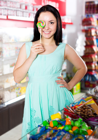 Funny young woman posing to photographer with lollypop at candies store