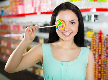 Portrait of  girl  with lollypop at candies shop Reklamní fotografie