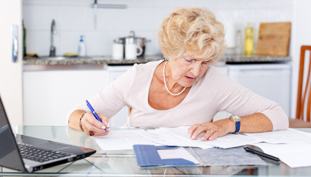 Mature woman filling up documents at kitchen table