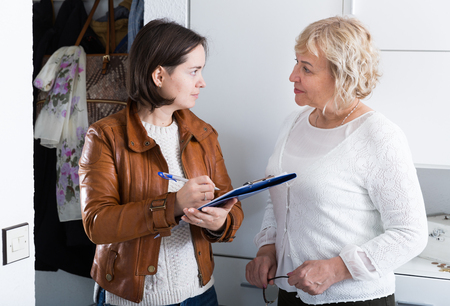 Interviewer interviews a mature woman at home, a social or commercial survey