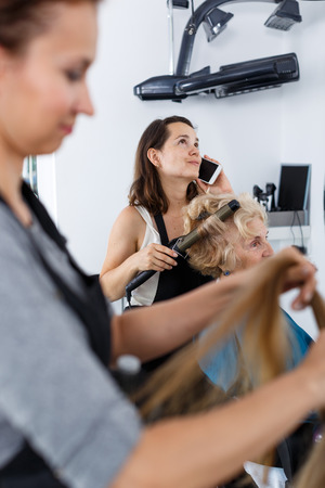 Distracted hairdresser emotionally talking on phone while making styling of senior woman at barbershop