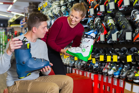 female assistant is helping man to trying on ski boots in store.