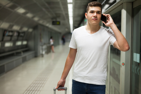 Young male passenger in casual clothing talking on his mobile phone in subway Imagens
