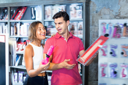 Glad cheerful smiling male and female purchasers touching big dildo in the modern shop
