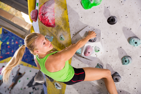 Young sporty woman training at bouldering gym without special climbing equipment