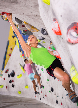 Young glad cheerful positive  sporty woman training at bouldering gym without special climbing equipment Reklamní fotografie