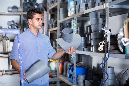 Male is choosing plastic trumpet in plumbing department in the building store.