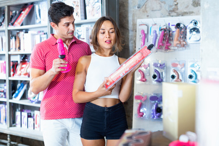 Glad positive male and female purchasers touching big dildo in the modern shop