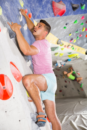 Male alpinist practicing indoor rock-climbing on artificial boulder without safety belts