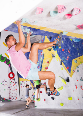 young man training at bouldering gym without special climbing equipment Banco de Imagens