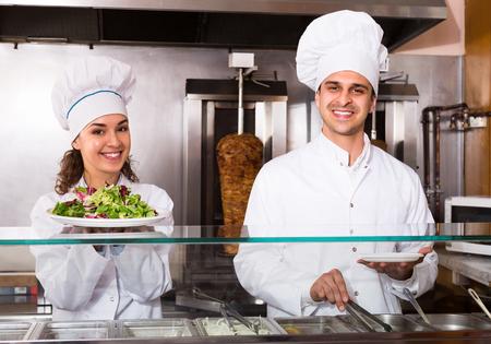 Two positive smiling chefs preparing kebab and vegetables salad at bistro 版權商用圖片