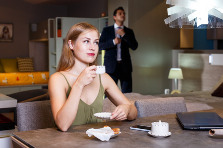 Young attractive woman enjoying cup of coffee in evening at home while spending time with boyfriend