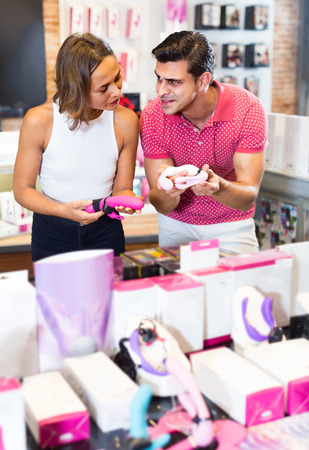 positive female and male purchasers touching in the modern sex shop different sexy toys