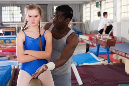 Male coach comforting sad teenage girl on gymnastic equipment at acrobatic hall Stock Photo
