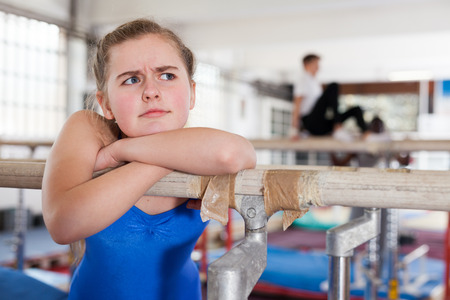 Portrait of sad teenage girl in gymnastic swimsuit posing near sports equipment in gym Reklamní fotografie - 116542312