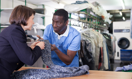 Manager of laundry working with woman client, receiving clothing for dry cleaning