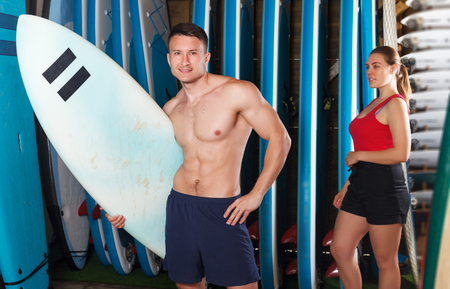 active young sporty couple with surf equipment in surf club