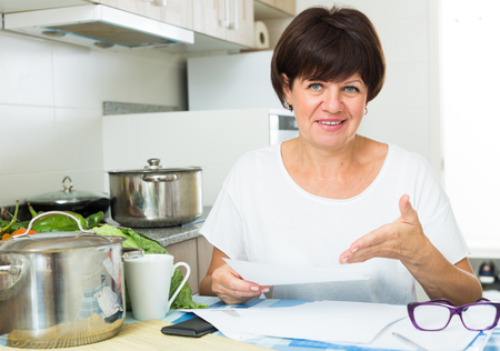 Cheerful retiree woman sitting on her kitchen and paying bills Foto de archivo