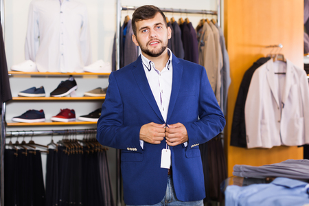 Young male customer choosing jacket in men clothes shop